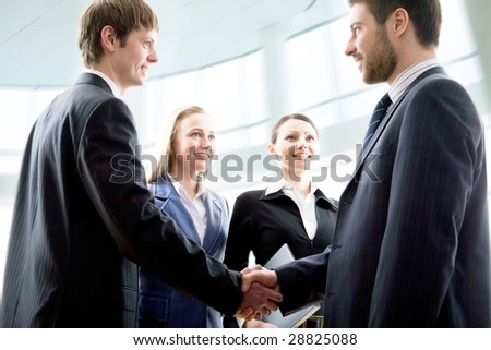 Modern businesspeople shaking hands in a modern office - stock photo