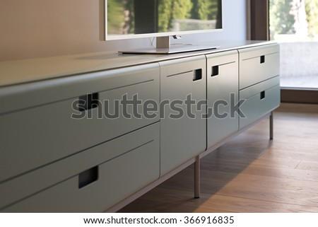 Modern living room interior, tv cabinet detail, selective focus - stock photo