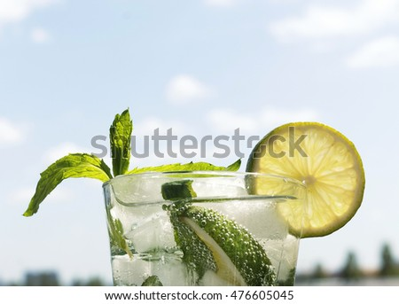 Mojito in a glass on a background of a modern city and blue sky with clouds. Closeup. Alcoholic or non-alcoholic cocktail.