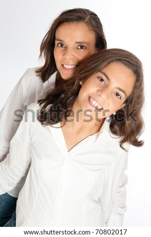 Mom and young teenage daughter looking at the camera - stock photo