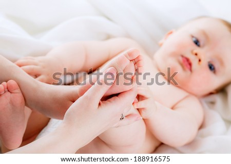 mom makes baby foot massage. isolation - stock photo