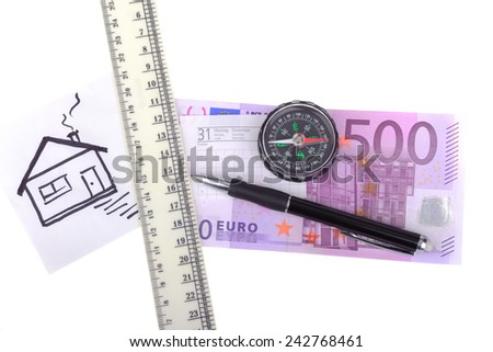 money five hundred euros compass with a red arrow and the recording sheet, pen and ruler, painted house isolated on white background number thirty-one - stock photo