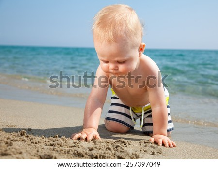 10 month baby boy wearing swimming shorts playing on a beach - stock photo