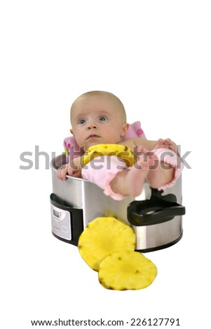 6 month baby girl lying in a saucepan with slices of pineapple - stock photo