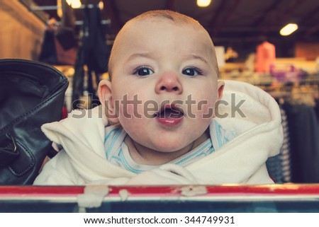 6 month old baby boy sitting in a shopping cart