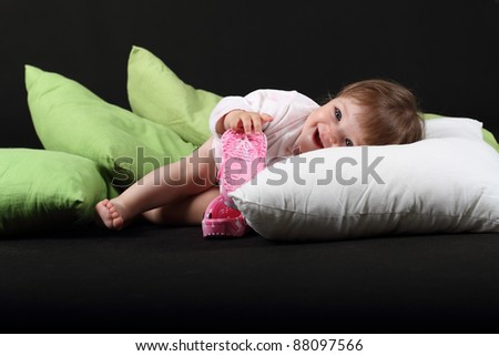 18 month old baby girl dressed in bath robe on green and white pillows on black background - stock photo
