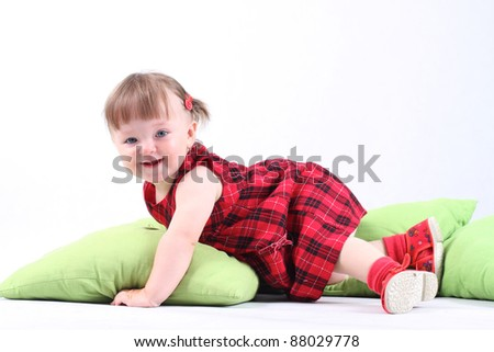 18 month old baby girl in red checked dress on green pillows on white background - stock photo