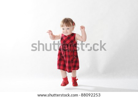 18 month old baby girl in red checked dress on white background - stock photo