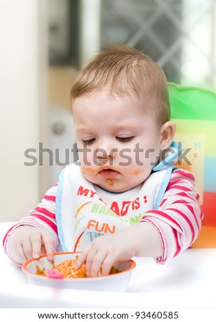 9 month old baby infant learning to eat by herself. - stock photo
