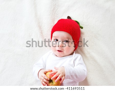 7 month old baby lying inbed with apple - stock photo