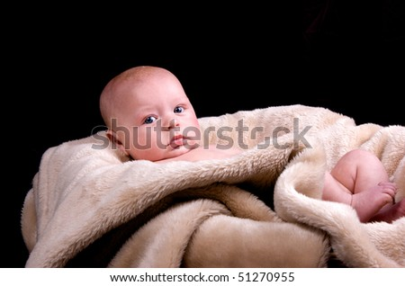 3 month old baby peering out from a blanket - stock photo