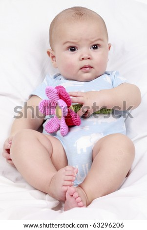 5 Month old baby playing with cuddly toy - stock photo