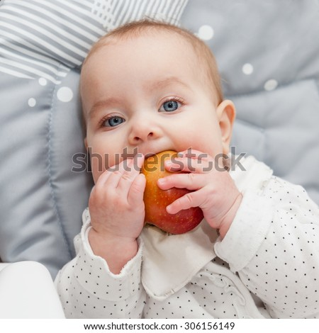 6 month old baby trying his first fruit: apple. Baby lead weaning. First food. Baby looking straight at the camera. Selective focus on baby head. - stock photo