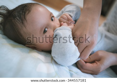 6 month old newborn mixed race Asian Caucasian boy being dressed by his Asian mother at home in a bedroom. Natural indoor lighting. - stock photo