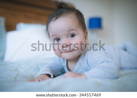 6 month old newborn mixed race Asian Caucasian boy plays on a bed. Natural indoor lighting. Cool tones - stock photo