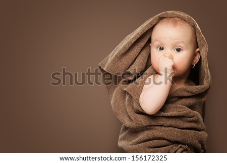 5 months baby girl in a brown blanket sucking thumb - stock photo