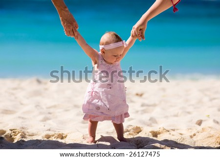 4 months baby girl on white sand tropical beach. - stock photo