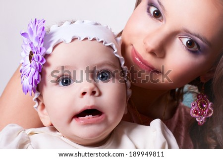 6 months baby girl surprised with a flower on her head, wearing a white blouse and a white ribbon on his head, in mother's arms - stock photo