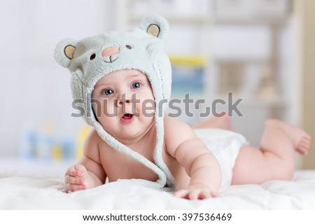 5 months baby girl weared in funny hat lying down on a blanket - stock photo