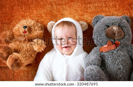 11 months baby in bear costume with plush toys - stock photo