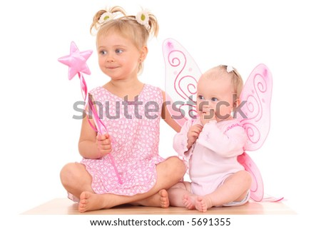 6 months little baby girl with pink wings and her sister - stock photo