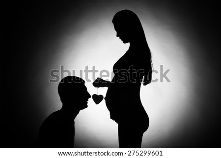 9 months of waiting for a miracle Young couple waiting for baby silhouette husband and pregnant wife man gently looks at the pregnant woman - stock photo