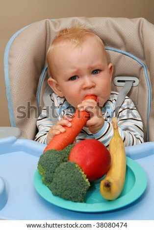 11 months old baby boy eating vegetables and fruits. - stock photo
