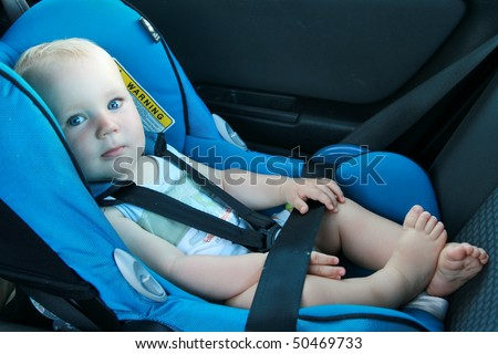 9 months old baby boy in a safety car seat. - stock photo