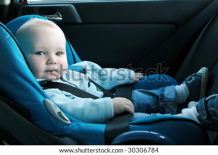 7 months old baby boy in a safety car seat. Safety and security - stock photo