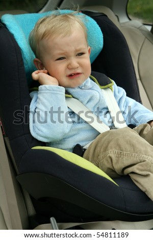 18 months old baby boy in car safety seat. Unhappy child crying. - stock photo