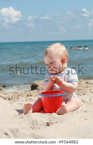 8 months old baby boy playing on a beach - stock photo