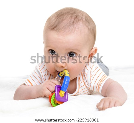 6 months old baby boy playing with his teether or toy - stock photo