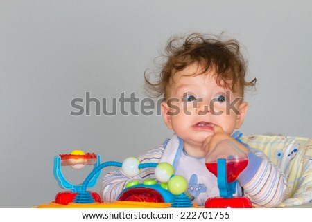 7 months old baby boy portrait while in walker with finger in his mouth. - stock photo