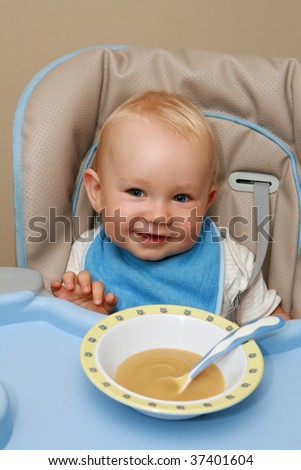 10 months old baby boy practice eating. Happy baby with a spoon. - stock photo