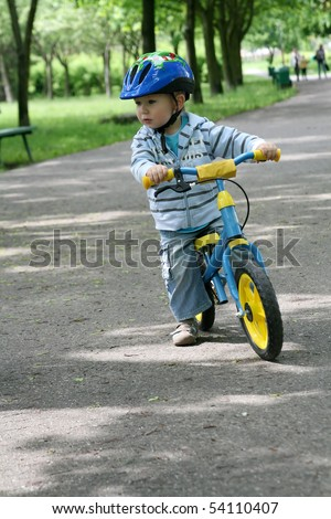 19 months old baby boy riding on his first bike in a helmet. Bike without pedals. Child learning to ride and balance on his two wheeler bike with no pedals. - stock photo