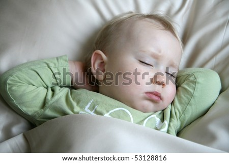 18 months old baby boy sleeping in bed and dreaming - stock photo