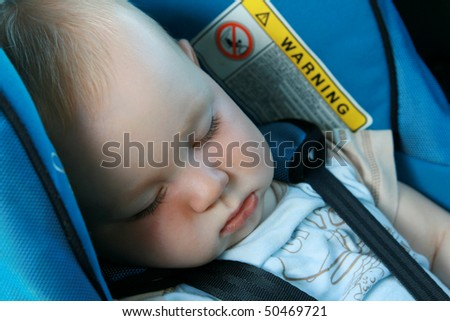 9 months old baby boy sleeping in car seat - stock photo