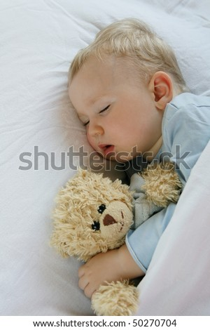18 months old baby boy slepping in bed with sweet teddy bear. Little baby dreamer. - stock photo