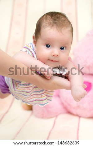 2 months old baby girl held on mother's arms. Shallow depth of field - stock photo