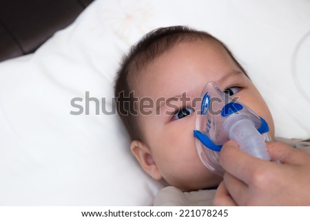 5 months old baby with respiratory disease, inhaling medication through spacer while laying in hospital bed - stock photo