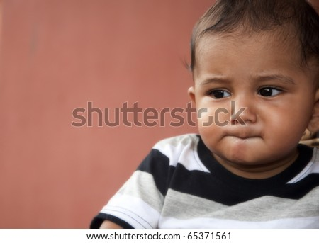 7 months old Indian origin asian baby boy kid thinking deeply. - stock photo