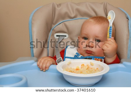 10 months old sad baby boy practice eating. Baby with a spoon. - stock photo