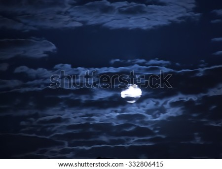 moon in the dark blue cloudy sky - stock photo