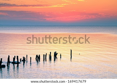 """Morning Glow"" - The sky radiates with color just before sunrise over Lake Huron in Michigan's Thumb.  - stock photo"