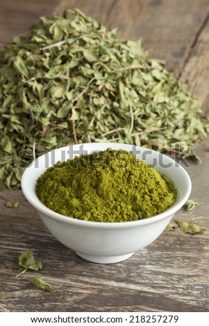 Moroccan henna leaves and powder in a bowl - stock photo