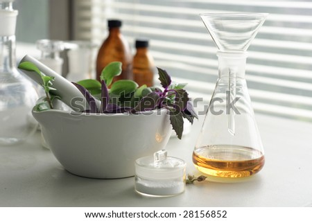 mortar and pestle  with herbs with a glass of alternative fuel