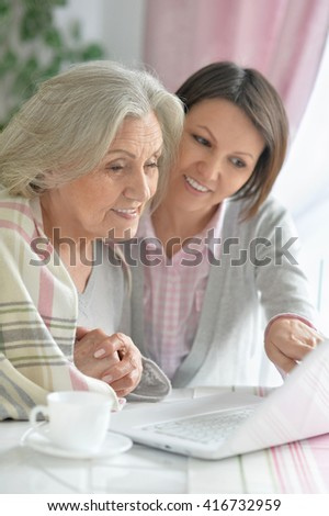 mother and adult daughter with laptop