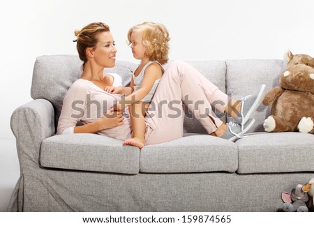 Mother and baby daughter playing on bad sofa 4