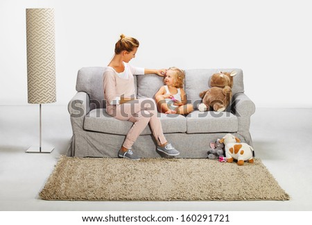 Mother and baby daughter playing on bad sofa 8