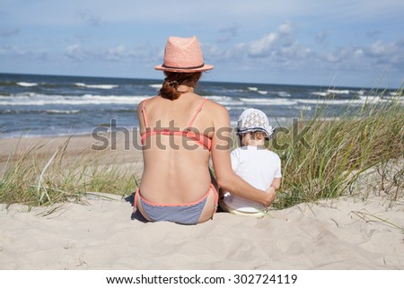 Mother and baby girl sitting on beach  - stock photo